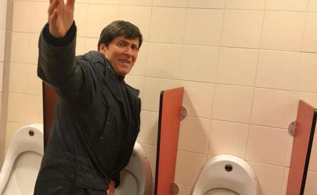 Gianni Morandi fotografato mentre fa pipì nel bagno di un Autogrill